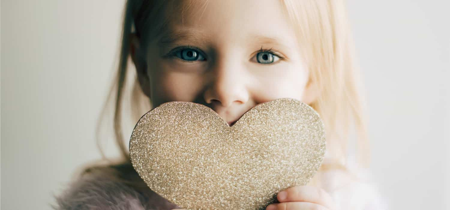 Girl with blonde hair holding a glitter heart in front of her mouth